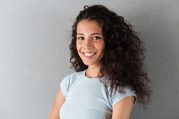Portrait de femme heureuse posant isolé sur gris