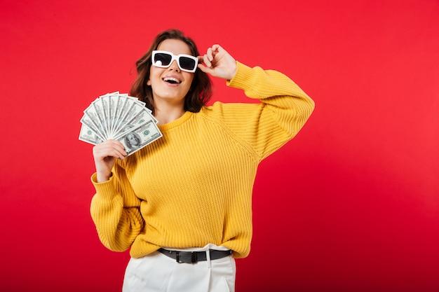 Portrait d'une femme heureuse en posant des lunettes de soleil