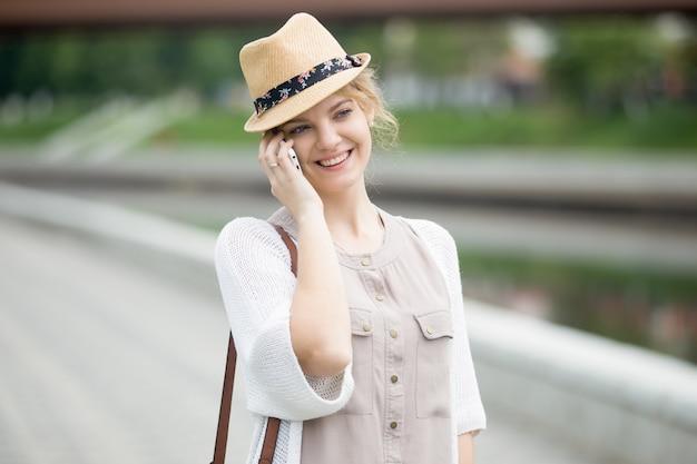 Portrait de femme heureuse qui parle sur un smartphone en marchant