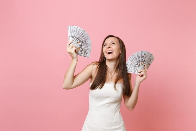 Portrait d'une femme heureuse qui rit en robe blanche tenant un paquet de dollars, de l'argent en espèces