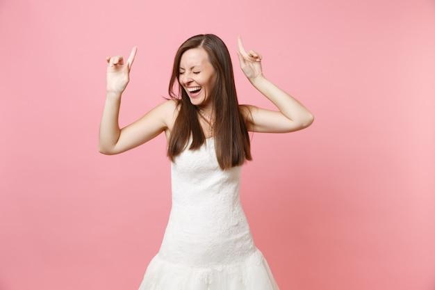 Portrait d'une femme heureuse qui rit avec les yeux fermés en robe blanche dansant pointant les doigts vers le haut