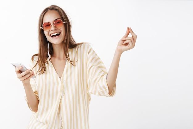 Portrait de femme heureuse ravie joyeuse dans des lunettes de soleil à la mode et chemisier holding smartphone souriant largement bénéficiant d'une grande qualité de musique dans les écouteurs