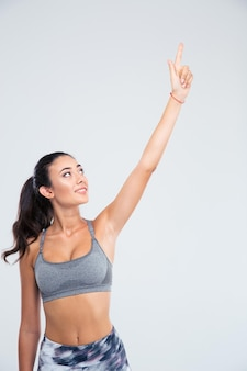 Portrait d'une femme heureuse de remise en forme doigt pointé vers le haut isolé sur un mur blanc