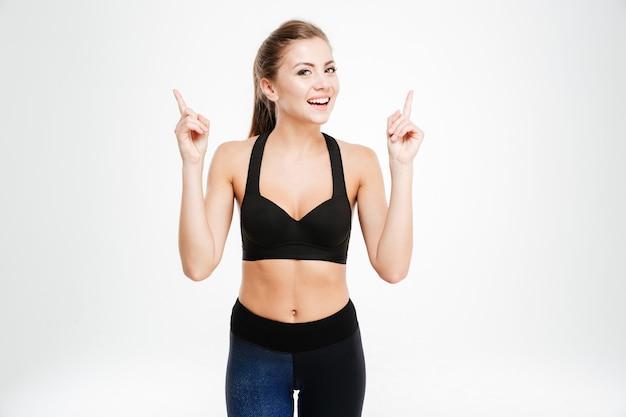 Portrait d'une femme heureuse de remise en forme pointant deux doigts vers le haut isolé