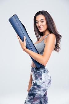 Portrait d'une femme heureuse de remise en forme tenant un tapis de yoga isolé sur un mur blanc