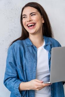 Portrait de femme heureuse en riant à l'aide d'un ordinateur portable