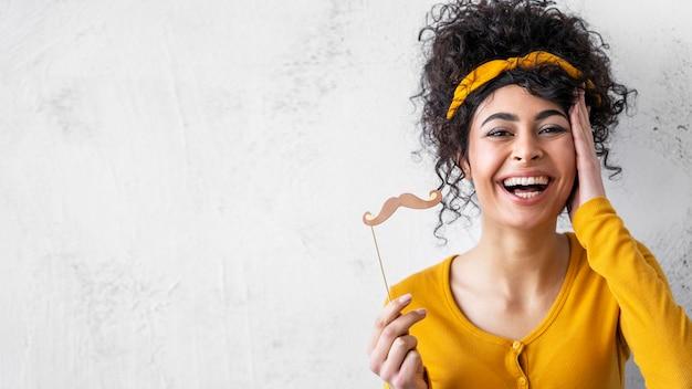 Portrait de femme heureuse en riant avec moustaches et espace copie