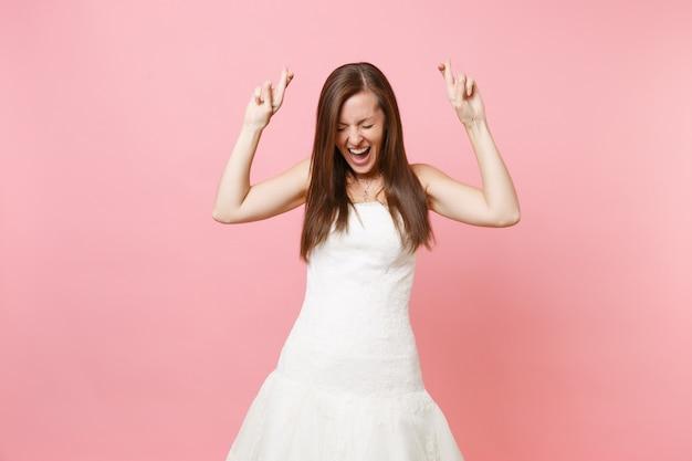 Portrait d'une femme heureuse en robe blanche attendant un moment spécial, croisant les doigts, les yeux fermés