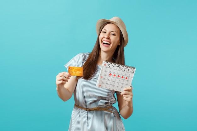 Portrait d'une femme heureuse en robe bleue, chapeau tenant une carte de crédit, calendrier des périodes, vérifiant les jours de menstruation isolés sur fond bleu tendance. concept gynécologique de soins médicaux. espace de copie.