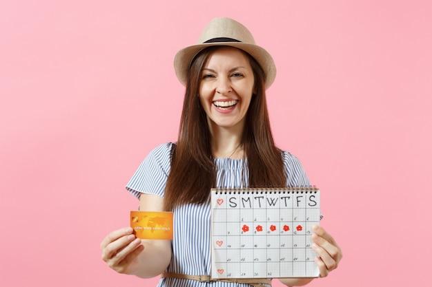 Portrait d'une femme heureuse en robe bleue, chapeau tenant une carte de crédit, calendrier des périodes, vérifiant les jours de menstruation isolés sur fond rose tendance. concept gynécologique de soins médicaux. espace de copie.