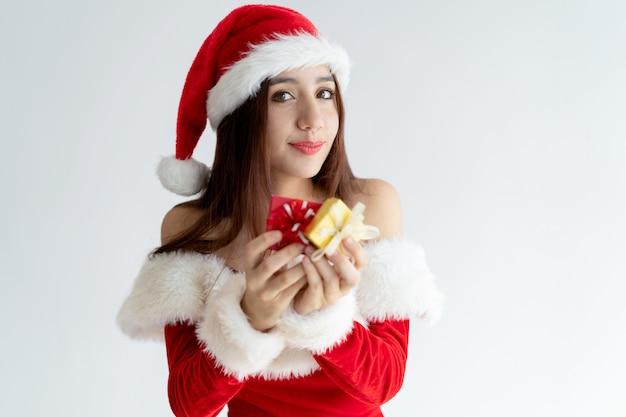 Portrait de femme heureuse en robe de père noël tenant des boîtes-cadeaux