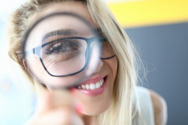 Portrait de femme heureuse s'amuser et regarder à travers la loupe. blonde séduisante dame