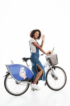 Portrait d'une femme heureuse avec un sac à provisions agitant en faisant du vélo isolé sur un mur blanc