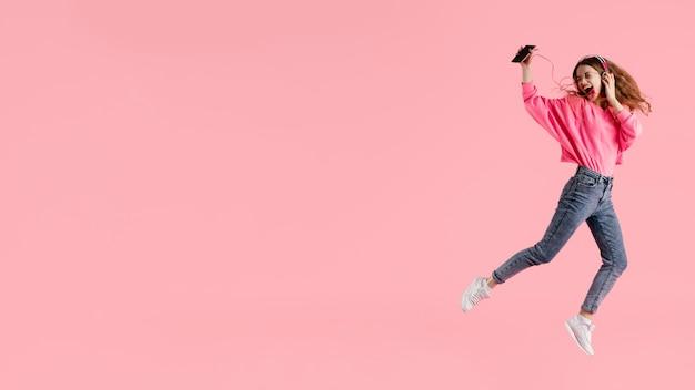 Portrait femme heureuse sautant et écoutant de la musique