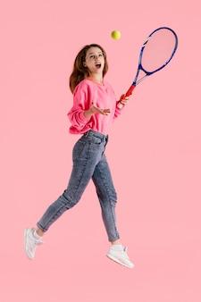 Portrait de femme heureuse sautant avec une raquette de tennis