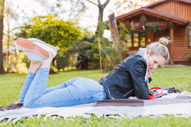 Portrait d'une femme heureuse se détendre dans le parc - jeune femme blonde souriante allongée sur l'herbe dans un jardin.