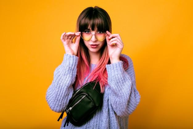 Portrait de femme heureuse sortie avec des poils roses ombrés tendance inhabituels posant au mur jaune, émotions surprises, pull confortable et lunettes de soleil vintage.