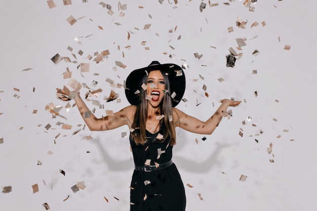 Portrait de femme heureuse sortie vêtue d'une robe noire du soir et un chapeau jetant des confettis sur un mur isolé avec de vraies émotions heureuses.