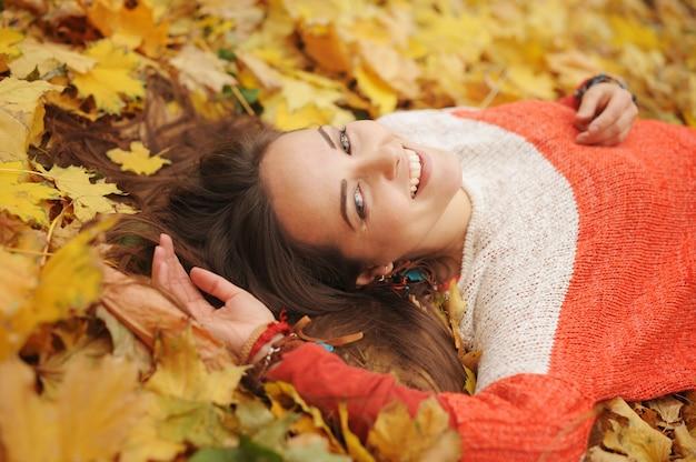 Portrait de femme heureuse souriante, allongée dans les feuilles d'automne, vêtue d'un pull à la mode, automne en plein air