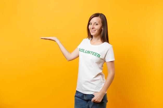 Portrait d'une femme heureuse souriante et satisfaite en t-shirt blanc avec inscription écrite bénévole titre vert isolé sur fond jaune. aide d'assistance gratuite volontaire, concept de travail de grâce de charité.
