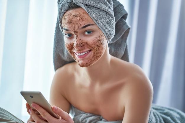 Portrait de femme heureuse souriante en serviette de bain avec gommage au café visage naturel après la douche pendant la journée spa