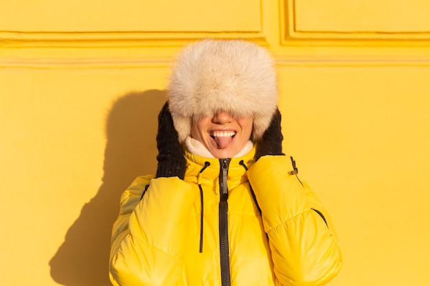 Portrait d'une femme heureuse avec un sourire en zabas blanc neige en hiver contre un mur jaune sur une journée ensoleillée dans un chapeau sibérien russe chaud