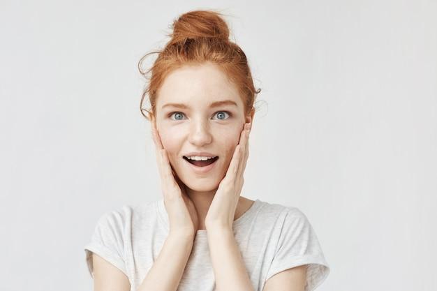 Portrait d'une femme heureuse surprise avec des cheveux foxy et des taches de rousseur.