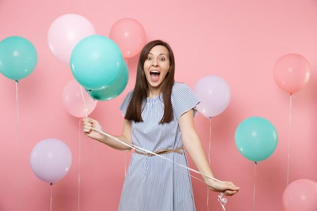 Portrait d'une femme heureuse surprise et ravie vêtue d'une robe bleue criant tenant des ballons à air colorés sur fond rose tendance lumineux. fête d'anniversaire, concept d'émotions sincères.