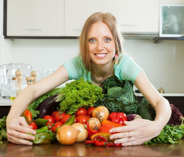 Portrait de femme heureuse avec tas de légumes