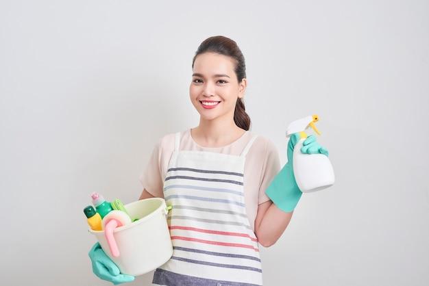 Portrait d'une femme heureuse tenant dans ses mains des produits de nettoyage en se tenant debout à la maison et en commençant à nettoyer.