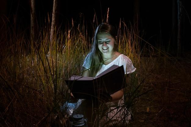 Portrait de femme heureuse tenant un livre rougeoyant dans la forêt de nuit
