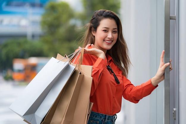 Portrait de femme heureuse tenant des sacs à provisions