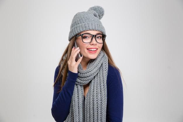 Portrait d'une femme heureuse en tissu d'hiver parlant au téléphone et isolée sur un mur blanc