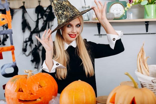 Portrait femme heureuse touche son chapeau et ludique de halloween