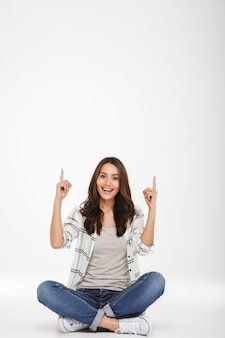 Portrait de femme heureuse en vêtements décontractés assis en posture de lotus sur le sol et en pointant les index vers le haut, isolé sur mur blanc