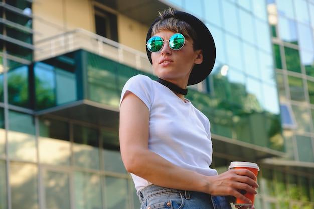 Portrait de femme hipster avec maquillage naturel et coupe courte bénéficiant de temps libre à l'extérieur