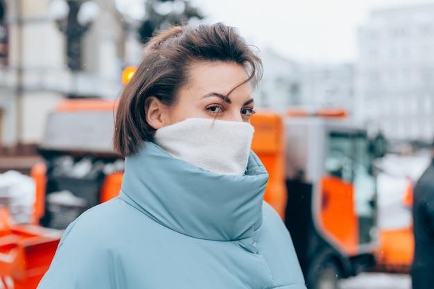 Portrait d'une femme en hiver sur le fond d'une souffleuse à neige