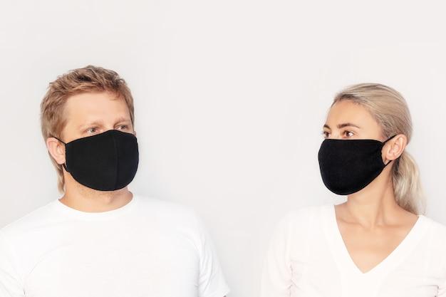 Portrait d'une femme et d'un homme adultes jeunes dans des masques médicaux sur un fond isolé