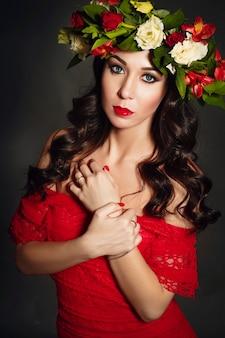 Portrait de la femme idéale avec une couronne de fleurs sur la tête. portrait d'art de mode. belle fille lumineuse de ressort avec des roses de fleurs