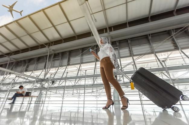 Portrait d'une femme immigrée musulmane portant un hijab marchant portant une valise, un billet et un passeport en mains voyageant en avion à l'aéroport.