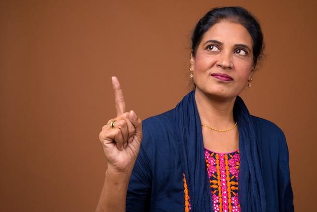 Portrait de femme indienne belle mature pensant et pointant le doigt vers le haut