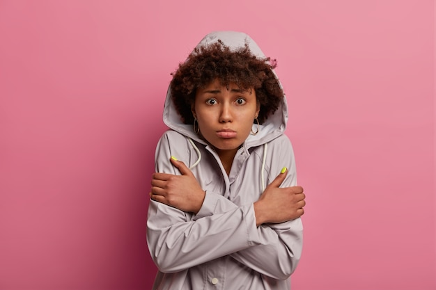 Portrait de femme insatisfaite croise les mains sur le corps, se sent gelé après avoir marché par temps humide, pose sur un mur rose, a une expression bouleversée, regarde un film d'horreur, voit une scène inattendue