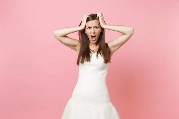 Portrait de femme insatisfaite irritée en robe blanche debout criant accroché à la tête