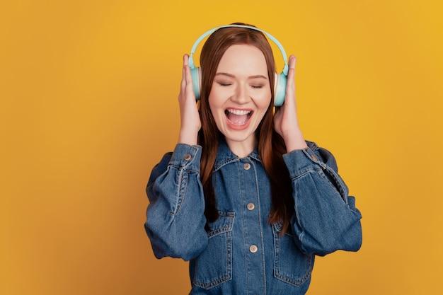 Portrait de femme insouciante porter des écouteurs profiter d'écouter de la musique sur fond jaune
