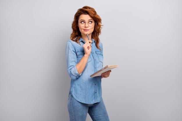 Portrait de femme intéressée d'esprit enseignant écrire conférence look copyspace penser pensées décider solution porter chemise jeans denim isolé sur mur de couleur gris