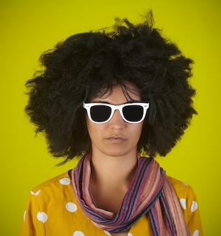 Portrait d'une femme intrigante indienne avec une coiffure afro bouclée et des lunettes blanches sur mur jaune