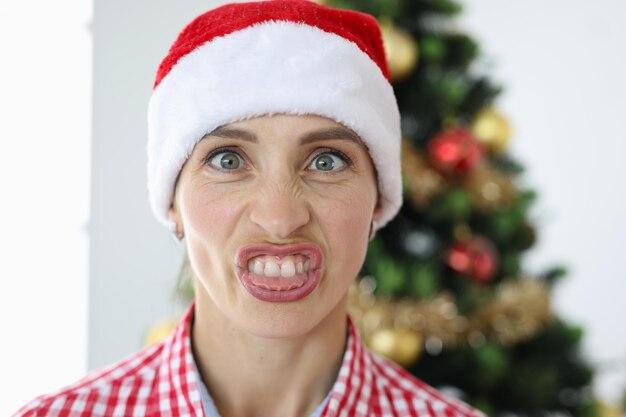 Portrait de femme irritée en chapeau de père noël sur fond d'émotions d'arbre de noël
