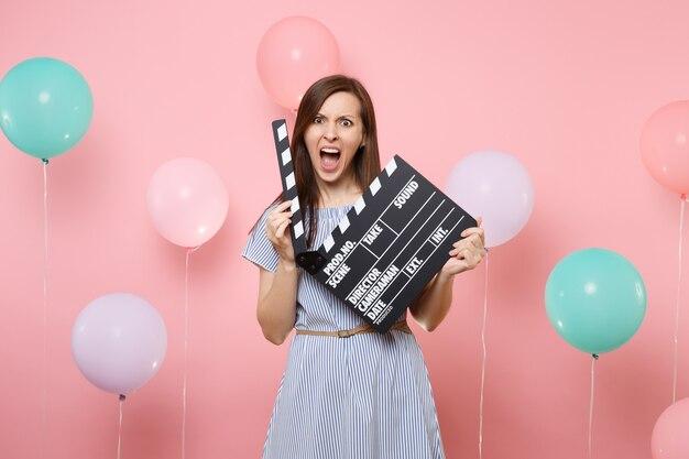 Portrait d'une femme irritée et choquée portant une robe bleue tenant un film noir classique faisant un clap sur fond rose avec des ballons à air colorés. fête d'anniversaire, émotions sincères.