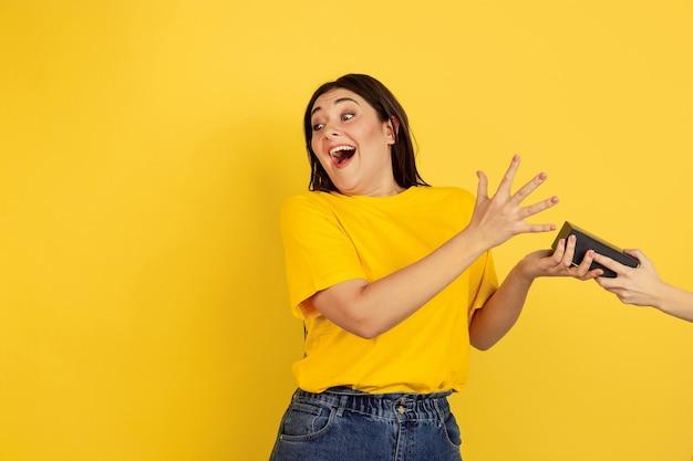 Portrait de femme isolé sur mur jaune studio