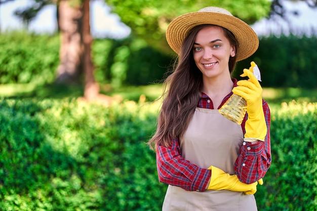 Portrait de femme jardinier avec vaporisateur pour arroser les plantes dans le jardin vert